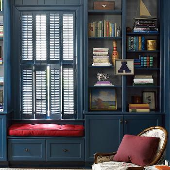 Lindsey Coral Harper - dens/libraries/offices - peacock blue built ins, peacock blue built in bookcases, built in window seat, double hung plantation shutters, peacock blue plantation shutters, peacock blue built in window seat, paisley chair, bamboo framed chair, bamboo framed paisley chair, blue and cream paisley chair, burgundy pillow, gray and ivory striped rug, striped area rug, window seat storage, window seat with storage drawers, raspberry pink seat cushion, painted plantation shutters, window shutters, double stacked interior shutters, bookcase decor, bookcase styling, leather bound books, wooden cigar box, traditional den, den, ceiling height built in bookcases, built in bookcases either side of window, built in bookcases next to window, window seat between built in bookcases, den window seat, office window seat, peacock blue cabinets, paneled office, paneled den, blue paneled office, blue paneled den,