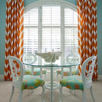 At Home in Arkansas - dining rooms - blue and orange dining room, turquoise and orange dining room, turquoise blue and orange dining room, arched window, chevron curtains, chevron drapes, orange curtains, orange drapes, orange chevron curtains, orange chevron drapes, glass top dining table, round dining table, round glass top dining table, blue and orange seat cushions, white dining chairs,
