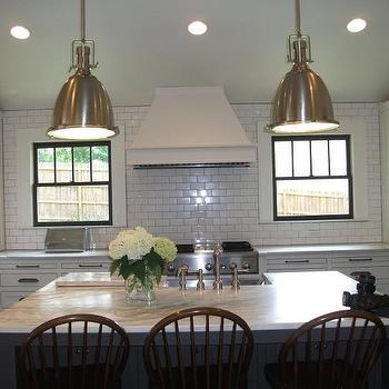 Twin Companies - kitchens - white cabinets, white double height cabinets, double height upper cabinets, black framed window, steel framed window, black window frame, subway tile, ceiling height subway tile, subway tile with gray grout, subway tile with dark grout, windows either side of range, windows next to range hood, windows beside stove hood, kitchen drawers, shaker front cabinets, shaker style cabinets, oil rubbed bronze hardware, cup pull hardware, under the counter microwave, below the counter microwave, stainless steel microwave, integrated microwave, vaulted ceiling, vaulted kitchen ceiling, ceiling height tile backsplash, ceiling height kitchen backsplash, marble counter, marble countertops, windsor counter stool, kitchen island sink, kitchen island apron sink, stainless steel farm sink, stainless steel farmhouse sink, stainless steel apron sink, gray kitchen island, two tone kitchen, dark hardwood floors, yoke pendant, polished nickel yoke pendant, polished nickel industrial pendant, pot lights, can lights, tapered range hood, kitchen subway tiles, kitchen subway tiles, oversized kitchen island, Benson Pendant,