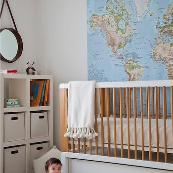 Sissy and Marley - nurseries - drum pendant, drum pendant with diffuser, dark hardwood floors, espresso hardwood floors, cowhide, cream cowhide, cream cowhide rug, modern white and wood crib, modern white crib with wooden rails, modern white crib with wooden spindles, white pom pom tasseled throw, pom pom trimmed throw, nursery world map mural, world map mural, world map mural behind crib, world map mural over crib, white open bookcase, modern white bookcase, white bookcase with baskets, white bookcase with storage baskets, round captains mirror, captains mirror, world map art, 2 tone crib,