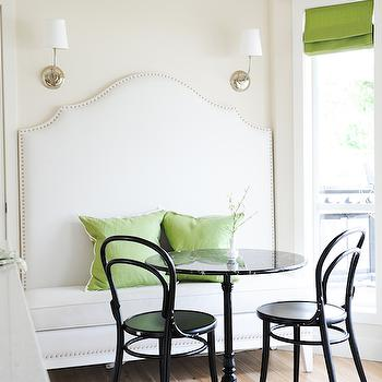 Tracey Ayton Photography - dining rooms - ivory and green dining room, white and green dining room, breakfast nook, built in banquette, dining banquette, built in dining banquette, banquette lighting, dining banquette lighting, nailhead banquette, green pillows, black cafe table, french cafe table, black french cafe table, black marble top table, black bentwood chairs, bay window, breakfast nook bay window, pea green roman shades, green roman shades, bay window window treatments,