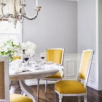 Domino Magazine - dining rooms - yellow chairs, yellow dining chairs, yellow french chairs, yellow french dining chairs, gray dining table, round dining table, round gray dining table, gray walls, wainscoting, dining room wainscoting,