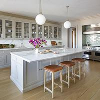 Gorgeous kitchen features glass-front cabinets and gray cabinets paired with white ...