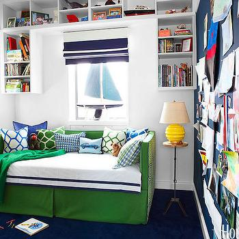 House Beautiful - boy's rooms: navy accent wall, navy blue accent wall, wall bulletin board, full wall bulletin board, built in cubbies, suspended cubbies, suspended cabinets, navy stripe roman shade, navy blue stripe roman shade, navy striped roman shade, navy blue striped roman shade, green daybed, skirted daybed, white and navy bedding, kids daybed, upholstered daybed, geometric pillows, wood top accent table, nautical bedroom, nautical boys room,