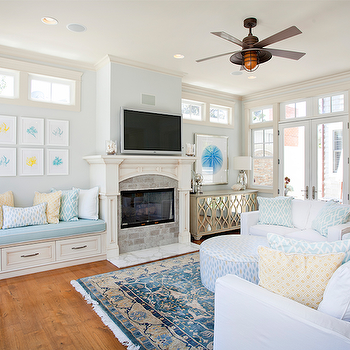 Erin Hendrick - living rooms - pale blue walls, light blue walls, built in bench, built in fireplace bench, storage bench, fireplace storage bench, storage bench in fireplace nook, transitional fireplace, whitewashed brick fireplace surround, tv over fireplace, flat screen tv over fireplace, aqua blue seat cushion, aqua blue and white geometric pillow, orange and white geometric pillow, nautical ceiling fan, nautical art, sea urchin art, mirror framed art, silver table lamp, mirrored buffet, lattice front mirrored buffet, french doors, transom window, transom window over french doors, white slipcovered sofa, white slipcovered settee, round ottoman, blue persian rug, symmetrical gallery wall, gallery wall over storage bench, mirrored cabinet, mirror fronted cabinet, fireplace built in bench, built in bench fireplace, built in bench at fireplace, blue persian rug, clerestory windows, fireplace tv, cottage living room, Oly Studio Elisabeth Buffet,