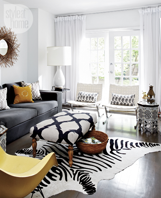 Style at Home - living rooms - white sheers, floor length sheers, french doors, living room french doors, white woven leather accent chair, white woven leather chair with chrome base, white leather chair with chrome base, black and white paisley pillow, black and white moroccan side table, black and white moroccan accent table, faux zebra hide, faux zebra hide rug, black and white moroccan ottoman, black and white moroccan pattern ottoman, black and white upholstered ottoman, woven basket, modern yellow chair, white table lamp, white table lamp with white drum shade, woven branch wall mirror, woven twig wall mirror, gray sofa, dark gray sofa, mustard velvet pillow, golden yellow pillow, gray and white geometric pillow, dark gray track arm sofa, track arm sofa, dark hardwood floors, trellis bench, trellis ottoman, cowhide rug, zebra cowhide rug, twig mirror, twigs mirror, round twigs mirror,