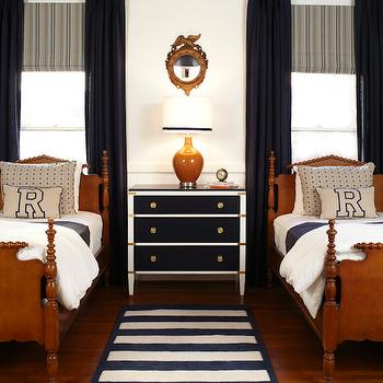 A Well Dressed Home - boy's rooms - hared bedroom, shared boys room, twin beds, matching twin beds, traditional twin bed, wooden bed frame, traditional wood bed, white bedding, navy bedding, white sheets, navy sheets, linen pillow with navy embroidery, linen pillow with navy embroidered letter, white nightstand with navy drawer fronts, white nightstand with navy drawer fronts and brass hardware, navy and white nightstand, navy and white nightstand with brass hardware, gold eagle mirror, eagle mirror, round eagle mirror, shared nightstand, shared bedside table, toffee colored table lamp, navy drapes, navy curtains, floor length drapes, floor length curtains, bed in front of window, bed below window, gray and navy striped roman shade, gray and navy striped window shade, navy blue ceiling, navy ceiling, dark blue ceiling, iron and rope chandelier, round iron chandelier, round iron rope hung chandelier, navy and white striped rug, shared nightstand navy ceiling navy blue ceiling,
