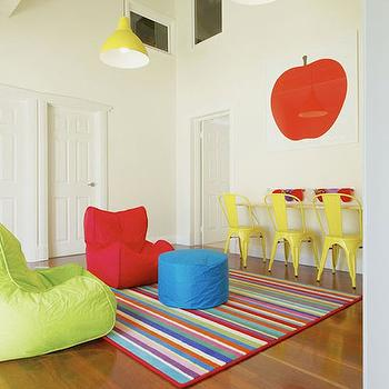 Collected Interiors - boy's rooms - kids playroom, childrens playroom, colorful playroom, multi colored playroom, yellow metal kids chair, yellow tabouret kids chair, child sized yellow tabouret chair, kids desk, built in kids desk, built in kids workstation, hardwood floors, striped playroom rug, multi colored striped rug, colorful striped rug, red beanbag chair, lime green beanbag chair, blue beanbag pouf, modern yellow pendants, contemporary yellow pendant, sloped ceiling, red apple art, kids apple art, modern red apple art print, yellow tolix chairs, high ceiling playroom, playroom high ceiling,