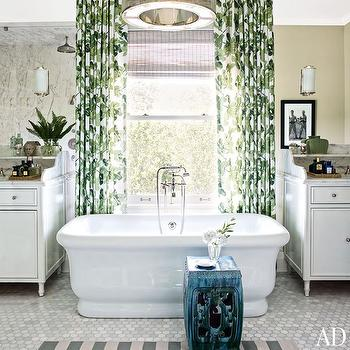 Architectural Digest - bathrooms - gray and white marble hex tile, marble hex tile, hexagonal marble tile, hexagonal marble tiled floors, gray and ivory striped rug, gray and ivory striped bath rug, teal garden stool, glazed teal garden stool, tub below window, bath under window, bathtub in front of window, freestanding tub, freestanding bath, pedestal tub, pedestal bath, floor mount faucet, floor mount tub filler, floor mount faucet with adjustable shower head, gray pinstriped roman shade, gray pinstriped window shade, fig leaf drapes, fig leaf fabric, fiddle leaf fig drapes, fiddle leaf fig curtains, white vanity, his and hers vanities, white footed vanity, sink sink vanity, marble counter, marble ledge, marble countertop ledge, vanity with marble counter and ledge, polished nickel and frosted glass sconce, contemporary polished nickel drum pendant, polished nickel drum chandelier, green leaf patterned drapes, leaf patterned curtains, bathroom drapes, bathroom curtains, bathtub in front of window,