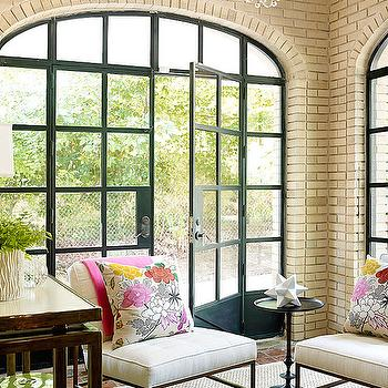 Traditional Home - living rooms: beige brick, brick wall, beige brick walls, steel and glass windows, steel and glass doors, white linen chairs, modern floral pillows, black accent table,