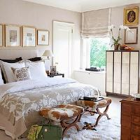 Veranda - bedrooms - serene bedrooms, elegant bedrooms, white and tan bedding, white and beige bedding, white headboard, gold leaf frames, art over headboard, swing arm sconces, headboard sconces, cowhide stools, cowhide ottoman,