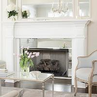 Leo Designs Chicago - living rooms: french living room, inset mirror, fireplace mirror, mirror fireplace surround, mirrored fireplace surround, fireplace surround, french armchairs, blue french chairs, french coffee table, square leg coffee table, gray rug,