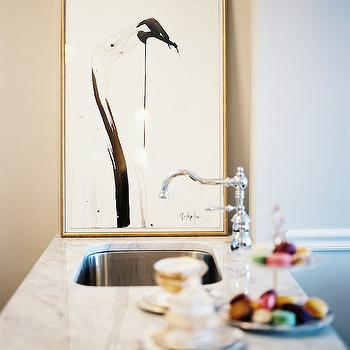 Lonny Magazine - kitchens - leaning art, gilt frame, black and white flamingo art, black and white flamingo print, undermount stainless steel sink, stainless steel single basin sink, hook spout faucet, polished chrome hook spout, traditional faucet, kitchen peninsula, marble counter, marble countertop, gray and white marble counter, peninsula, kitchen peninsula, peninsula sink, kitchen peninsula sink,