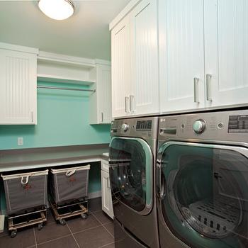 Homes by Tradition - laundry/mud rooms - gray front loading dryer, gray front loading washer, front load washer, front load dryer, side by side front loading washer and dryer, gray floor tile, gray tiled floor, beadboard cabinets, white beadboard cabinets, beadboard cabinetry, nickel hardware, nickel cabinet pulls, gray square tiled floors, laundry hamper on wheels, laundry hamper on casters, gray counter, gray countertop, laundry room folding counter, folding counter, laundry folding counter, drying rail, clothes drying rail, beadboard laundry room cabinets, beadboard cabinet doors, laundry sorters, skylight, laundry room skylight, skylight laundry room, tiffany blue walls, tiffany blue laundry room,