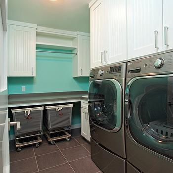 Homes by Tradition - laundry/mud rooms - gray and turquoise laundry room, gray front loading dryer, gray front loading washer, front load washer, front load dryer, side by side front loading washer and dryer, gray floor tile, gray tiled floor, beadboard cabinets, white beadboard cabinets, beadboard cabinetry, nickel hardware, nickel cabinet pulls, gray square tiled floors, laundry hamper on wheels, laundry hamper on casters, gray counter, gray countertop, laundry room folding counter, folding counter, laundry folding counter, drying rail, clothes drying rail, beadboard laundry room cabinets, large laundry room, laundry room layout, spacious laundry room, tiffany blue walls, beadboard cabinet doors, laundry sorters, skylight, laundry room skylight, skylight laundry room,