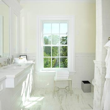 Sotheby's Realty - bathrooms - white and yellow bathroom, waterworks stool, bathroom stool, waterworks baths tools, waterworks bathroom stools, half tiled wall, pale yellow paint, light yellow paint, grid tile backsplash, stacked tile backsplash, framed mirrors, framed vanity mirrors, honed marble, honed marble countertops, white marble floor, oval vanity sink, hot and cold faucets, master bath, sunny master bath,