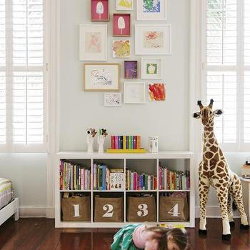 Charleston Magazine - girl's rooms: plantation shutters, window shutters, interior window shutters, hardwood floors, red hardwood floors, white shelving unit, white cubby shelving, low white shelving unit, stuffed giraffe, faux zebra hide rug, zebra print cowhide rug, zebra cowhide rug, numbered storage bins, books, kids bookshelf, large stuffed giraffe, gallery wall, kids gallery wall, colorful gallery wall, girls room gallery wall, gallery wall between windows, number bins, numbered bins, kids bookcase, kids bookshelf, white expedit,