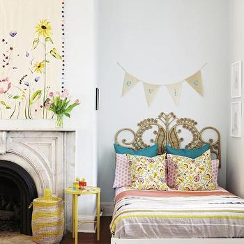 Charleston Magazine - girl's rooms - vintage rattan headboard, peacock headboard, vintage rattan peacock headboard, rattan peacock headboard, striped bedding, striped kids bedding, teal green pillow, pink polka dot pillow, floral pillow, yellow stool, yellow striped woven basket, striped woven basket, carved marble fireplace, arched marble fireplace, arched marble fireplace surround, floral tapestry, contemporary floral tapestry, pom pom trimmed floral tapestry, tapestry over fireplace, name banner, kids name banner, red hardwood floors, faux zebra hide rug, zebra cowhide rug, faux zebra cowhide rug, name banner,