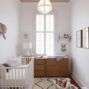 Charleston Magazine - nurseries - white crib, contemporary white crib, white crib with rounded corners, moroccan shag rug, beni ourain rug hardwood floors, moses basket, gender neutral nursery, neutral nursery, monochromatic nursery, campaign chest, campaign dresser, side by side campaign chest, plantation shutters, tall window, window shutters, interior window shutters, tall ceilings, diamond shaped pendant, frosted glass diamond shaped pendant, grasscloth ceiling, grasscloth wallpapered ceiling, wallpapered ceiling, grass cloth wallpapered ceiling, white table lamp, white ceramic table lamp, stuffed animal faux taxidermy, stuffed elephant faux taxidermy,