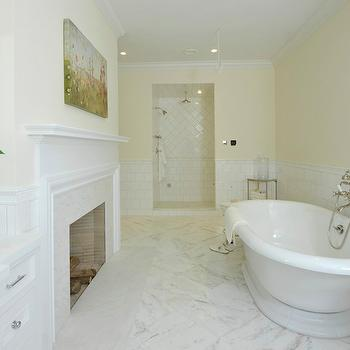 Sotheby's Realty - bathrooms - white and yellow bathroom, half tiled wall, pale yellow paint, light yellow paint, bathroom fireplace, bath fireplace, fireplace in bathroom, fireplace bathroom, soaking bathtub, wall mount tub filler, walk in shower, open shower, open walk in shower, shower surround, diamond pattern shower surround, diamond shower surround, shower pencil rail, shower chair rail, large subway tiles, rain shower head, master bath ideas, master bathroom ideas,
