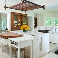 Beautiful kitchen features pot rack suspended from ceiling over white kitchen ...