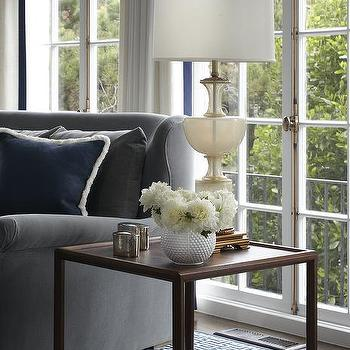 Lauren Ranes - living rooms - wood end table, end tables, x end table, x base end table, tall glass lamp, gray velvet sofa, rolled arm sofa, gray rolled arm sofa, gray velvet sofa, navy pillows, french doors, wall of doors, wall of french doors, white curtains, navy trim curtains,