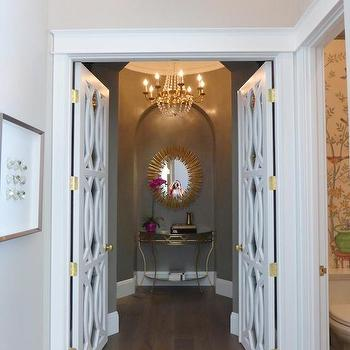 Annie Vincent Interiors - entrances/foyers - arched niche, arched alcove, domed hallway, domed entryway, domed foyer, round foyer, round hallway, domed ceiling, antiqued gold console table, antiqued gold demi lune console, gold console table with mirrored shelves, oval gold mirror, oval gold leafed mirror, taupe walls, dark taupe walls, dark taupe wall color, geometric paneled doors, white geometric doors, statement doors, contemporary white doors, brass door hardware, antiqued gold chandelier, gold crystal beaded chandelier, antiqued gold beaded chandelier, geometric doors, mirrored doors, geometric mirrored doors, mirrored paneled doors, paneled mirrored doors, foyer nook, arched nook, arched foyer nook, foyer arched nook, Arteriors Prescott Gold Iron Oval Mirror, Worlds Away Treillage Console,