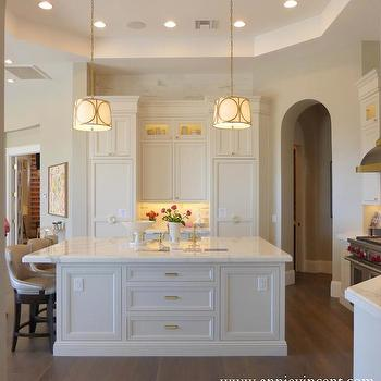 Annie Vincent Interiors - kitchens - archway, arched doorways, hardwood floors, white cabinets, white cabinetry, white inset cabinets, inset kitchen cabinetry, kitchen island, kitchen island overhang, white marble counters, white marble countertops, brass cabinet pulls, brass hardware, cabinet front refrigerator, paneled refrigerator, hidden fridge, hidden refrigerator, concealed fridge, concealed refrigerator, tray ceiling, tray kitchen ceiling, octagonal tray ceiling, brass trimmed kitchen pendant, brass trimmed drum pendant, under cabinet lighting, double stacked cabinets, double stack upper cabinets, glass accent cabinets, pale taupe counter stool, taupe counter stool, counter overhang, countertop overhang, kitchen tray ceiling, octagonal ceiling, octagon ceiling, octagon tray ceiling, oversized island, concealed fridges, hidden fridges,