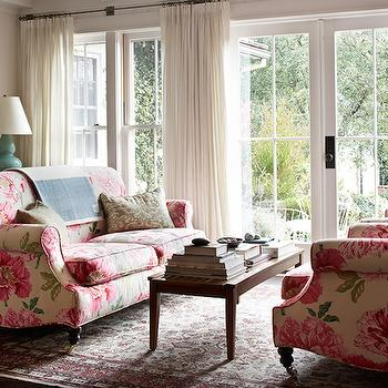 Kristen Panitch Interiors - living rooms - sofas facing each other, face to afce sofas, pink sofa, chintz sofa, pink chintz sofa, tiered console table, espresso console table, vertical wall paneling, wall of french doors, white sheer curtains, baby blue lamp, baby blue gourd lamp,