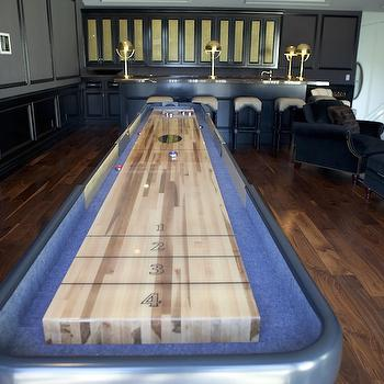 Bravo TV - media rooms - game room, game room ideas, wainscoting, game room wainscoting, black wainscoting, black bar, game room bar, black marble, black marble counters, black marble countertops, paneled doors, shuffleboard table, abacus barstools, black barstools, black abacus barstoools,