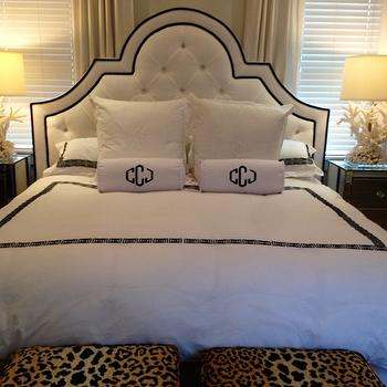 Luxe Report - bedrooms - leopard stools, leopard print stools, leopard ottomans, leopard print ottomans, black and white headboard, white tufted headboard, white headboard black piping, monogrammed bolster pillows, mirror nightstands, mirrored nightstands, coral table lamp, white coral table lamp, black and white bedding, black and white hotel bedding, ivory curtains, ivory drapes,