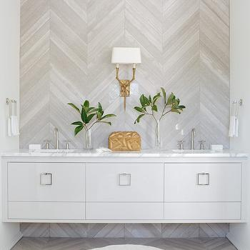 Atlanta Homes & Lifestyles - bathrooms - herringbone wall, accent wall, bathroom accent wall, accent wall bathroom, herringbone tiled wall, herringbone floor, floating vanity, floating washstand, gray floating vanity, gray floating washstand, square pulls, square hardware, square ring pulls, white marble countertop, his and her sinks,