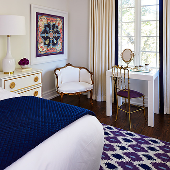 The World According to Jessica Claire - bedrooms - cream walls, cream bedrooms, walls, window cornice, cream curtains, cream drapes, mini parsons desk, desk in front of window, gold chair, gold desk chair, french chair, purple ikat rug, white and gold nightstand,