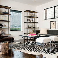 Kriste Michelini Interiors - living rooms - iron and wood bookcase, gray tufted sofa, acrylic stools, zebra cowhide rug, glass top coffee table, origami coffee table, brown armchair,