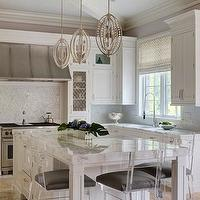 Incredible kitchen with white cabinets accented with nickel hardware and white ...