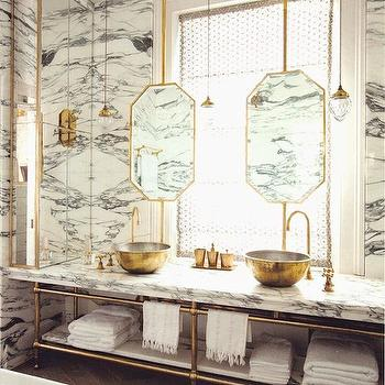 The World of Interiors - bathrooms - brass washstand, brass sink vanity, brass vanity sink, double vanity sink, brass double vanity sink, gold sinks, gold bowl sinks, gold vessel sinks, round bowl sinks, round gold sinks, offset faucets, brass faucets, brass gooseneck faucets, offset vanity faucets, white and grey marble, white and grey marble countertops, suspended mirrors, hanging mirrors, gold mirrors, gold vanity mirrors, octagon mirrors, octagonal mirrors, gold octagon mirrors, gold octagonal mirrors, mirror in front of window, hanging light pendants, brass and glass pendants, door moldings, geometric moldings, geometric door moldings, herringbone floor, mirrored cabinet, mirrored linen cabinet,