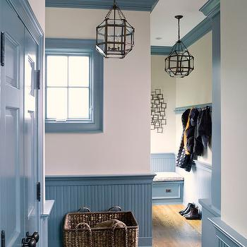 SB Long Interiors - laundry/mud rooms - hallway mud room, mud room, pale greige walls, pale greige wall color, blue beadboard, beadboard half wall, beadboard paneled walls, beadboard wainscoting, beadboard paneling, blue closet doors, blue window trim, blue crown molding, seagrass basket, built in storage bench, mud room bench, mud room storage bench, coat hooks, industrial iron lantern, iron and glass lantern, suzanne kasler morris chandelier, mudroom beadboard, beadboard mudroom, blue moldings, blue window moldings, mudroom lanterns,