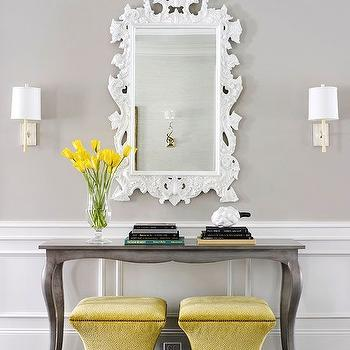 BHG - entrances/foyers - yellow and gray foyer, yellow and gray entry, yellow and gray entryway, white baroque mirror, baroque mirror, nickel wall sconce, contemporary nickel wall sconce, silver gray console, silver gray console table, silver cabriole leg console, cabriole leg console table, raised panel wainscoting, half wall wainscoting, gray walls, gray wall color, foyer wainscoting, entryway wainscoting, white wainscoting, yellow flowers, stacked books, yellow ottoman, yellow storage ottoman, dark hardwood floors, glossy black floors, ornate white mirror, foyer vignette, entry vignette, entryway vignette, paneled half wall, paneled lower wall, foyer wainscoting, entry wainscoting, half painted walls, white baroque mirror, gray console table, cabriolet console table, gray cabriolet console table,