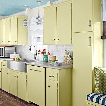 Lowes - kitchens - blue ceiling, blue kitchen ceiling, blue painted ceiling, yellow kitchen, yellow kitchen cabinets, flat front cabinets, yellow cabinetry, nickel hardware, travertine silver laminate counters, travertine silver laminate countertops, stainless steel apron sink, stainless steel farm sink, stainless steel farmhouse sink, gooseneck faucet, kitchen window seat, green and white striped cushion, green pillow, green geometric pillow, mini pendant lights, gooseneck faucet, hardwood floors, subway tile, subway tile backsplash, woven shade, woven blind, yellow and blue kitchen, wood effect floor tile, faux wood floor tile, faux timber floor tile, tile that looks like hardwood floors, tile that looks like hardwood, yellow cabinets, travertine silver laminate, window seat kitchen, wood like tiles, tile that looks like wood,