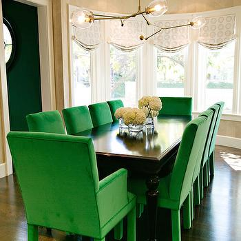 Evars and Anderson - dining rooms - long dining room, green dining chairs, black dining table, dining table with turned legs, black dining table with turned legs, brass and glass pendant, brass and glass chandelier, curved windows, curved dining room windows,