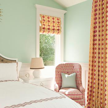Thornton Designs - bedrooms - seafoam green walls, seafoam wall color, wainscoting half wall, paneled half wall, orange and pink drapes, orange and pink curtains geometric pink and orange drapes, geometric pink and orange curtains, geometric pink and orange roman shade, pink button tufted chair, pink button tufted accent chair, seafoam green pillow, white nightstand, white lacquered nightstand, white table lamp, round white table lamp, pink embroidered duvet, pink embroidered bedding, brown button tufted headboard, brown diamond button tufted headboard, sunburst mirror, sunburst dot mirror, gold sunburst dot mirror, french doors, bedroom french doors, contemporary white nightstand,