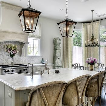 French kitchen features iron lanterns illuminating gray island topped with curved ...