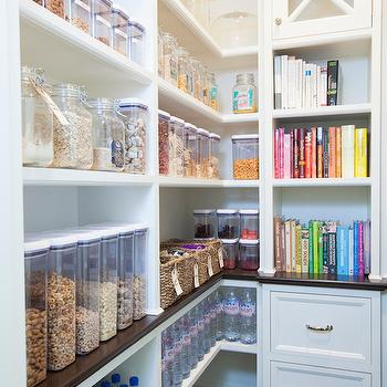 Walk-in pantry features built-in shelving filled with labeled clear food ...