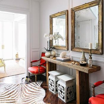 Lonny Magazine - entrances/foyers - chic foyers, herringbone floor, wood herringbone floor, herringbone wood floor, beveled mirrors, gold mirrors, gold beveled mirror, foyer tables, reclaimed console table, reclaimed wood console table, red chairs, red accent chairs, red square back chairs, red french chairs, white garden stools, chinoiserie stool, white chinoiserie stool, zebra rug, foyer wainscoting, full wall wainscoting, floor to ceiling wainscoting, foyer rug, red and gold rooms, red and gold foyer,