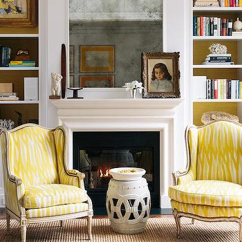 Lonny Magazine - dens/libraries/offices - yellow chairs, yellow accent chairs, wingback chairs, yellow wingback chairs, rope stool, white rope stool, den, den fireplace, den builtins, den bookcases, den bookshelf, den bookshelves, fireplace built ins, fireplace bookcases, fireplace bookshelves, painted backs of shelves, antiqued mirror, inset mirror, inset fireplace mirror, built in bookcases, built in bookshelves,