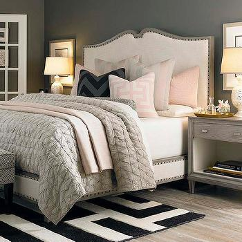 bedrooms: french style bed, linen upholstered bed, linen bed with nailhead trim, gray wash bed with nailhead trim, grey wash bed, dark gray walls, dark gray wall color, gray walls, gray wall color, pink and gray bedroom, pink pillow sham, pink and white geometric pillow, pink and gray striped pillow, blush pink pillow, white sheets, gray duvet, gray voile duvet, gray voile quilt, gray nightstand, gray single drawer nightstand, gray bedside table, gold mercury glass lamp, gold table lamp, matching table lamps, gray wash hardwood floors, grey wash hardwood floors, black and white rug, black and white geometric rug, geometric rug, art over nightstand, pink and gray bedding, pink and gray pillows, gray quilt,