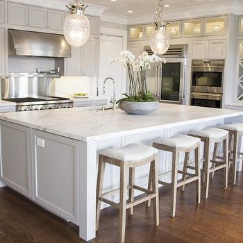 Stunning L-shaped kitchen with light gray cabinets with beaded doors pairing with ...