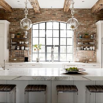 Loft kitchen with rustic wood beams accented with clear glass globe pendants ...