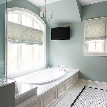 Steffanie Gareau - bathrooms - gray green walls, gray green wall color, marble tiled floors, marble bathroom floors, basketweave tiled rug, basketweave tiled carpet, marble basketweave tiled rug, marble basketweave tiled carpet, arched window, arched bathroom window, bath below window, bath under window, bathtub below window, tub under window, oval drop in tub, paneled bath surround, paneled tub surround, paneled bathtub surround, bathroom tv, bathroom television, tv over tub, tv over bath, tv over bathtub, hook spout bath faucet, hook spout tub faucet, damask shade, gray damask roman shade, chandelier over tub, chandelier over bath, nickel chandelier, bathroom chandelier, nickel chandelier with shades, tiled rug, marble tiled rug, bathtub chandelier, paneled bathtub, wainscoted bathtub, wainscoted tub, blue roman shade,