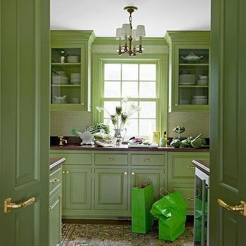 Meg Braff Interiors - kitchens - Benjamin Moore - Forest Moss - green kitchen, green kitchen cabinets, moss green cabinets, mossy green cabinets, green butlers pantry, raised front cabinet doors, raised front cabinets, brass hardware, hardwood floors, persian rug, small persian rug, kitchen persian rug, mahogany counter, mahogany countertop, wallpapered backsplash, sash window, sash kitchen windows, painted window trim, painted window frame, glass front cabinets, glass front upper cabinets, butlers pantry, brass chandelier, brass chandelier with white shades, traditional butlers pantry, brass cabinet pulls, brass hardware, green cabinets, green moldings, wallpaper backsplash, brass door knobs,